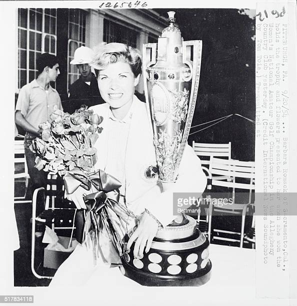 Attractive Barbara Romack insurance saleswoman from Sacramento Cal is shown with the trophy and flowers presented to her after she defeated Mickey...