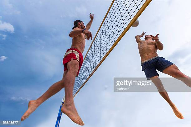 attractive beach volley action in mid-air - beachvolleybal stockfoto's en -beelden