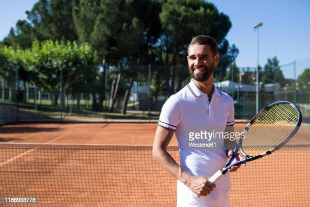 attractive bearded man in tennis wear holding racket and looking away - ラケット ストックフォトと画像