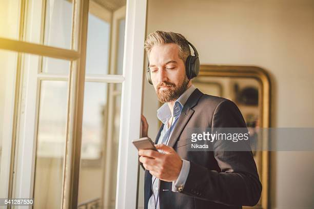 Attractive bearded man listening to music
