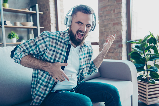 Attractive, bearded man sitting on the couch in living room, having headphones on his head, listening his favorite music, singing a song dreaming like playing guitar 924375490