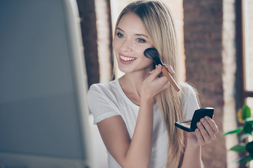 Attractive beautiful charming joyful glad woman wearing white t-shirt is applying blusher on her cheekbones in front of mirror at home 926321388