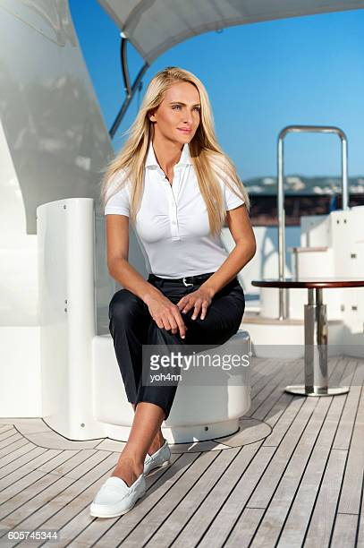 Attractive blond woman sitting on top of yacht