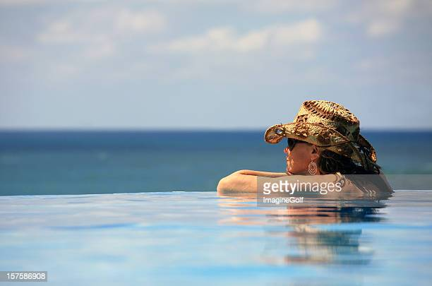 Attractive Blonde Caucasian Woman Relaxing in Infinity Pool