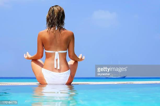 jolie blonde femme méditer au bord de la piscine. - femme blonde en maillot de bain vue de dos photos et images de collection