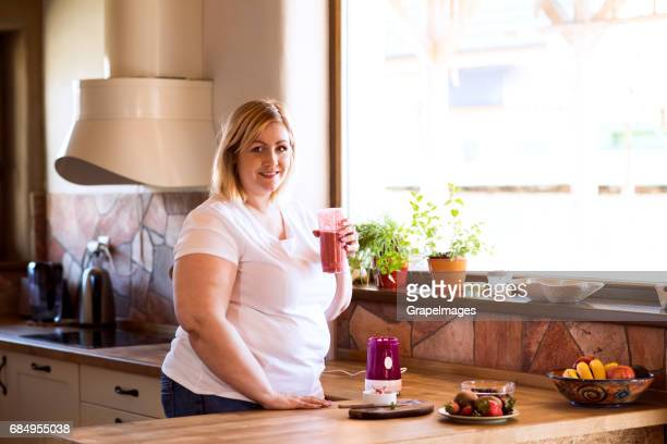 Attractive blonde overweight woman at home in her kitchen drinking delicious healthy smoothie.