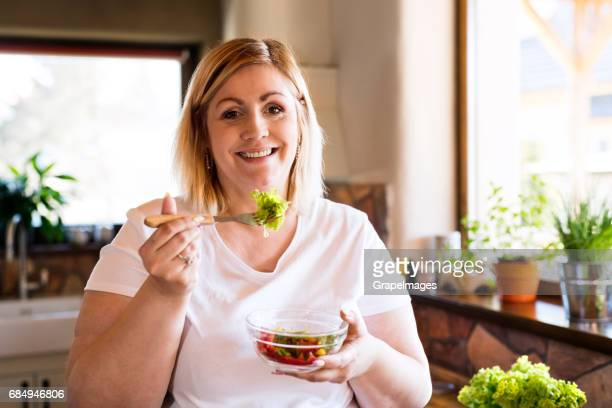 Attractive blonde overweight woman in white t-shirt at home eating a delicious healthy vegetable salad in her kitchen.