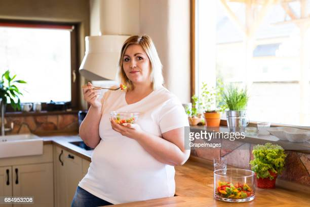attractive blonde overweight woman in white t-shirt at home eating a delicious healthy vegetable salad in her kitchen. - big fat white women stock pictures, royalty-free photos & images