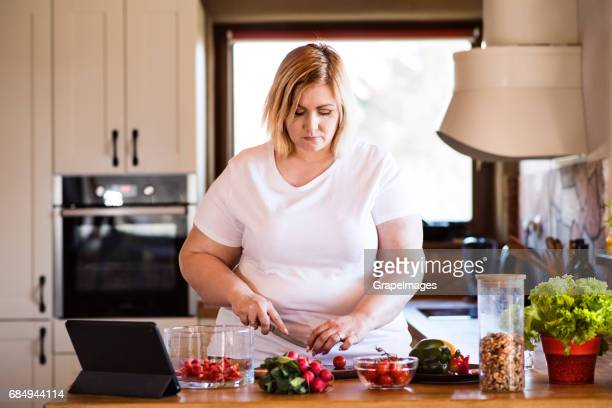 attractive blonde overweight woman in white t-shirt at home preparing a delicious healthy vegetable salad in her kitchen. - big fat white women stock pictures, royalty-free photos & images