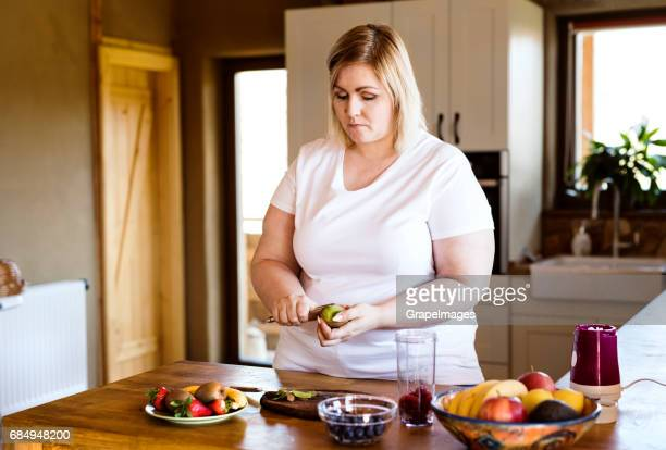attractive blonde overweight woman in white t-shirt at home preparing a delicious healthy smoothie in her kitchen. - big fat white women stock pictures, royalty-free photos & images