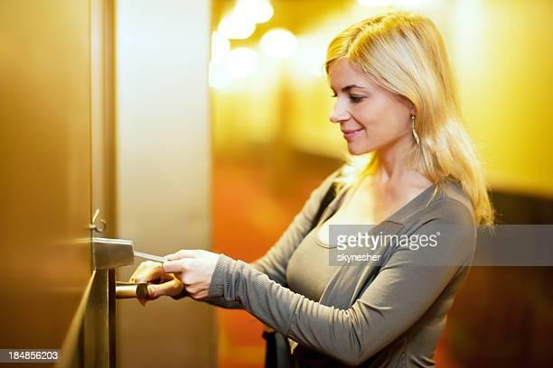 Jolie blonde femme ouverture sa chambre d'hôtel.
