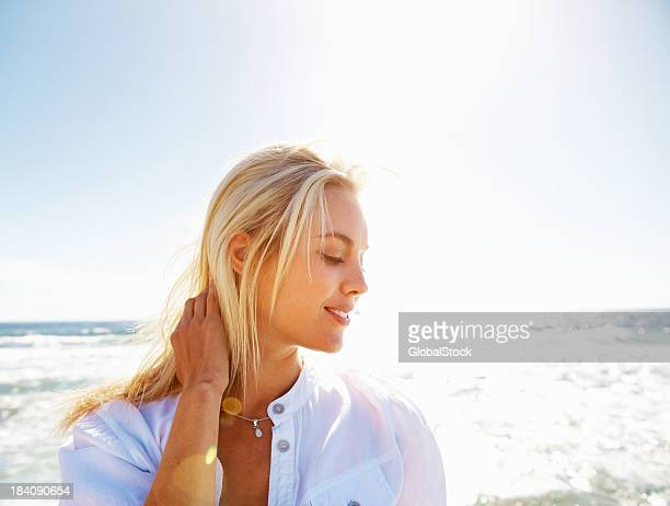 Attractive blonde woman posing for photo on beach