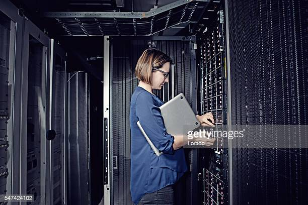 attractive brunette adult female employee working in internet server room - cooling rack stock photos and pictures
