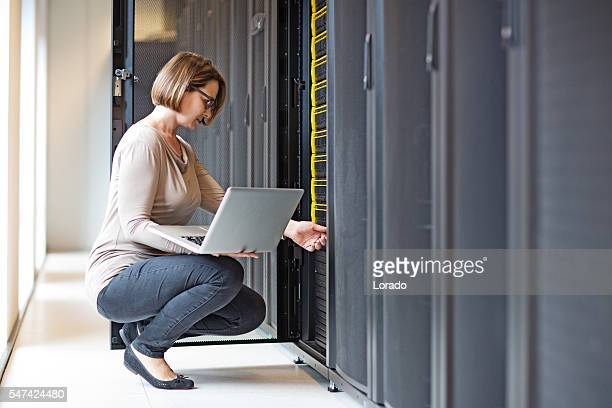 attractive brunette adult female employee working in internet server room - storage compartment stock pictures, royalty-free photos & images