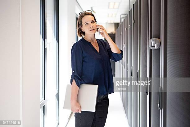 Attractive brunette adult female employee working in internet server room