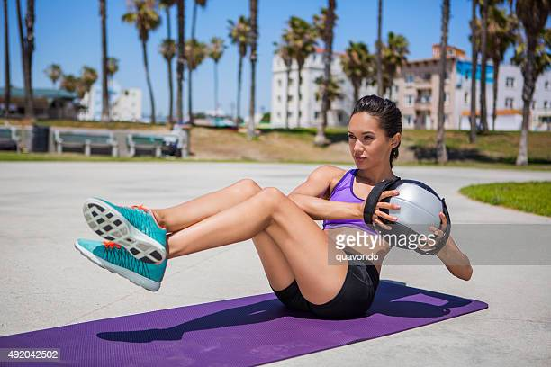 attractive brunette female athlete doing medicine ball - medicine ball stock pictures, royalty-free photos & images