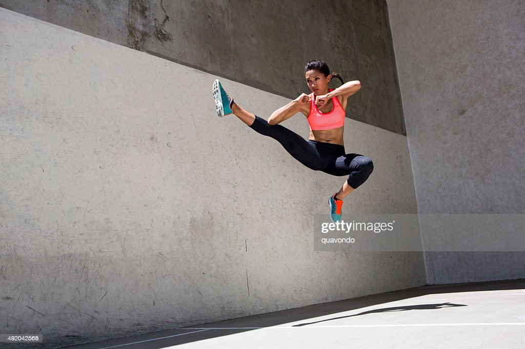 Attractive brunette female athlete jumping in the air : Stock Photo