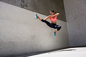 Attractive brunette female athlete jumping in the air