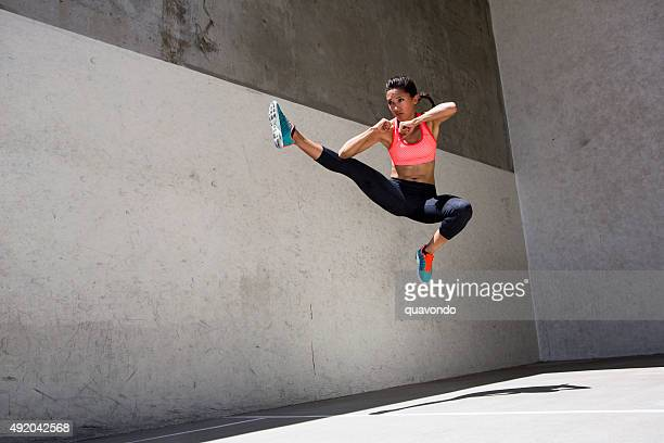 attractive brunette female athlete jumping in the air - kicking stock pictures, royalty-free photos & images