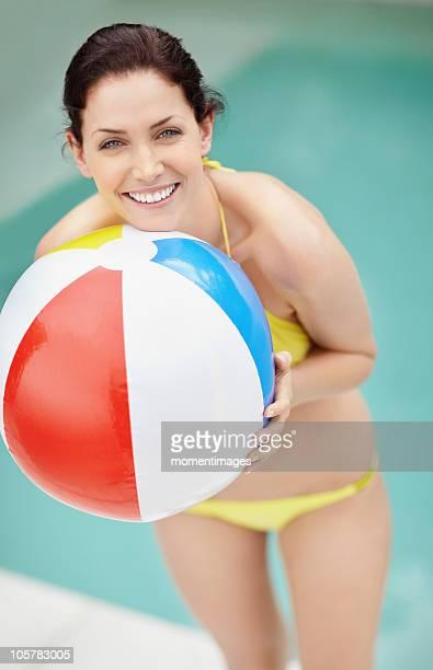 Attractive brunette holding a beach ball