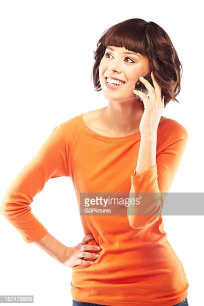 魅力的なブルネットの女性彼女の携帯電話で話している。絶縁ます。 - オレンジ色のシャツ ストックフォトと画像