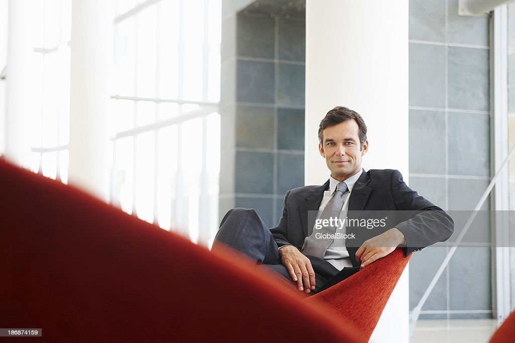 Attrayant Homme d'affaires assis et souriant en toute confiance : Photo