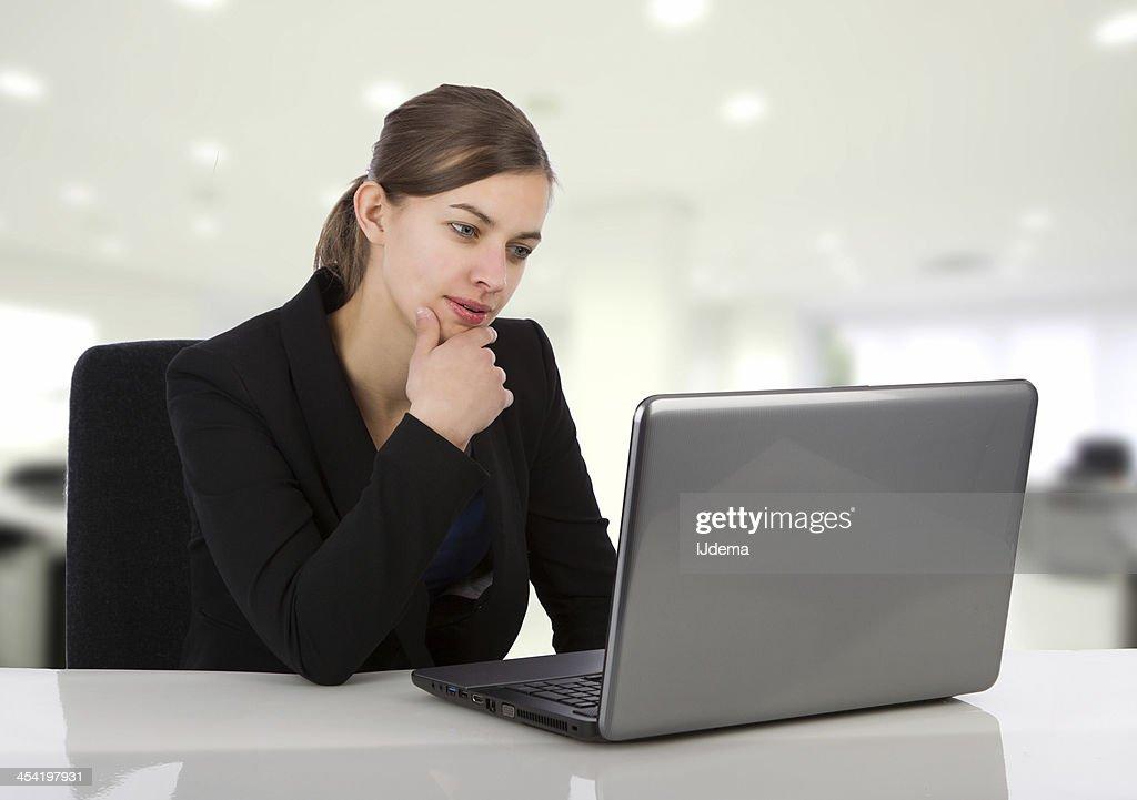 Atractiva mujer de negocios mirando a su pantalla de la computadora portátil : Foto de stock