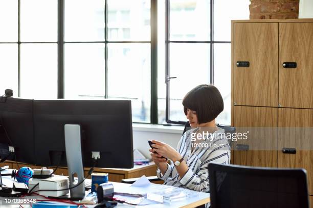 attractive businesswoman at desk using mobile phone - wasting time stock pictures, royalty-free photos & images
