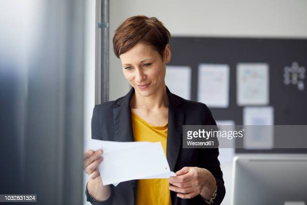 attractive businesswoman standing in office, readiing document - e mail - fotografias e filmes do acervo