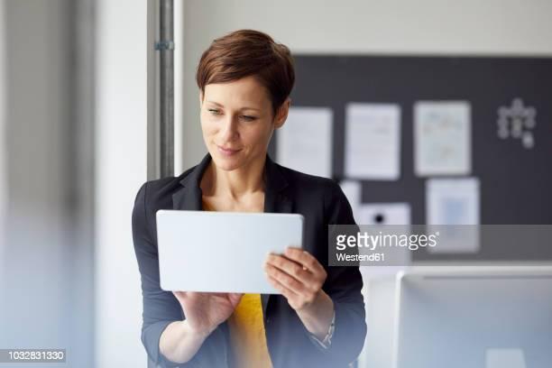 attractive businesswoman standing in office, using digital tablet - usare un tablet foto e immagini stock