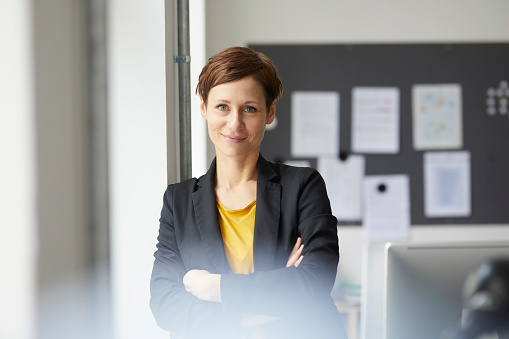Attractive businesswoman standing in office with arms crossed - gettyimageskorea