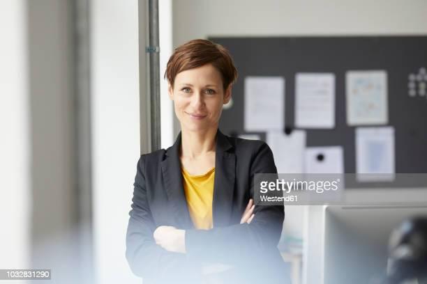 attractive businesswoman standing in office with arms crossed - goed gekleed stockfoto's en -beelden