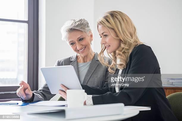 Attraktive Geschäftsfrau mit Ältere Frau Kollegin mit Tablet