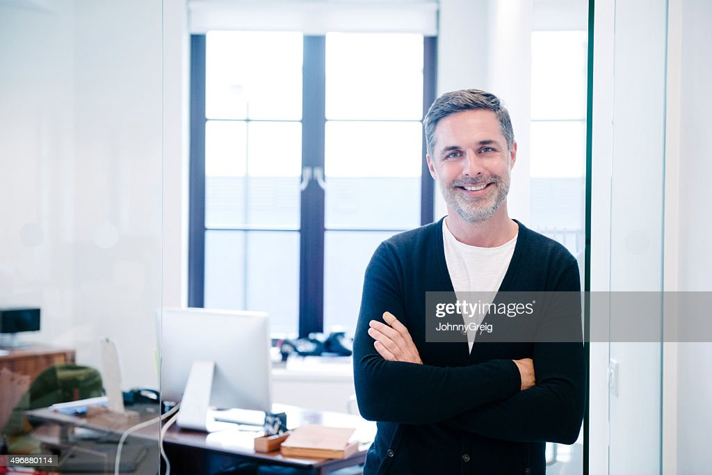 Attractive casual businessman in modern office, arms folded : Stock Photo