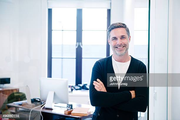 Attractive casual businessman in modern office, arms folded