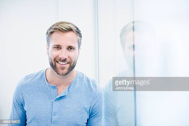 Attractive casual businessman with beard in modern office, portrait