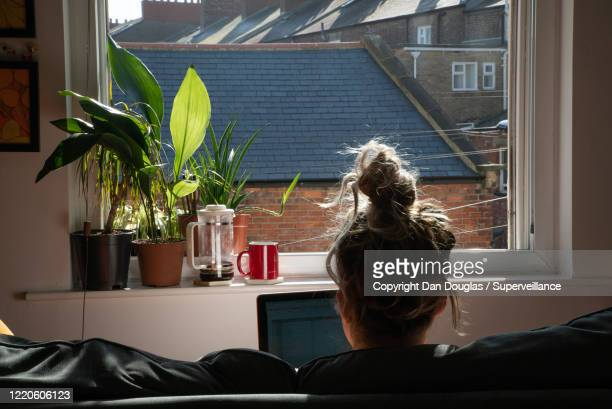 attractive casual hippie woman working from home in her pyjamas - window stock pictures, royalty-free photos & images