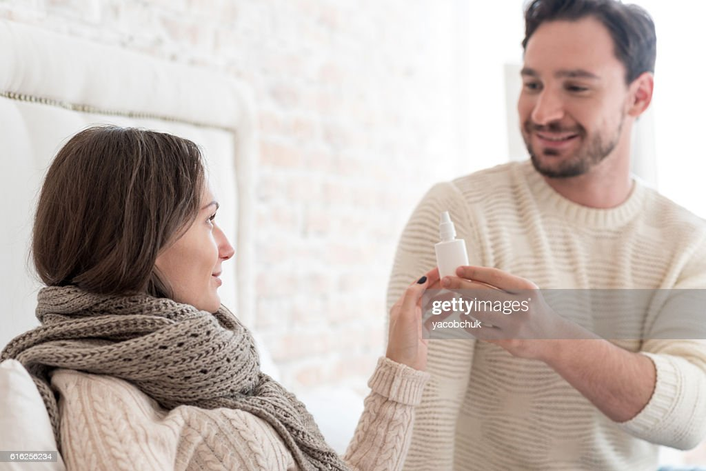 Attractive cheerful man giving his girlfriend nose drops : Stock Photo