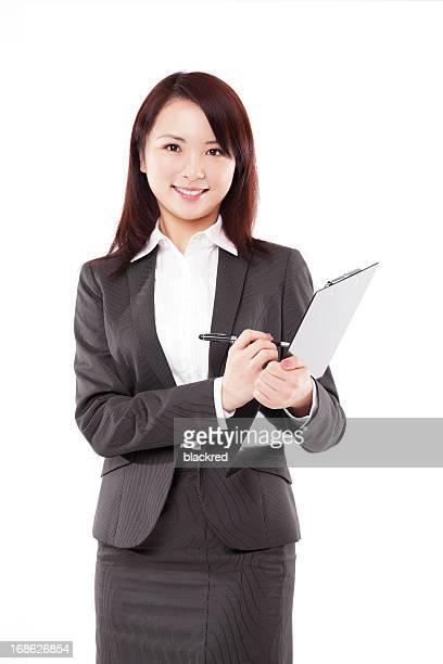 魅力的な中国のビジネスウーマンの書き込みにクリップボードの笑顔、白色背景