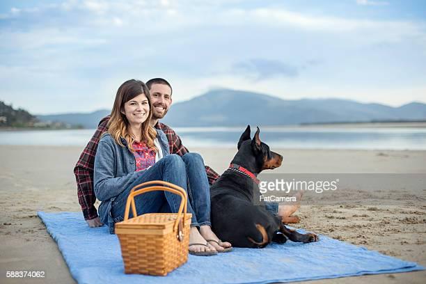 Attraktives paar und Ihr Hund mit einem Picknick auf