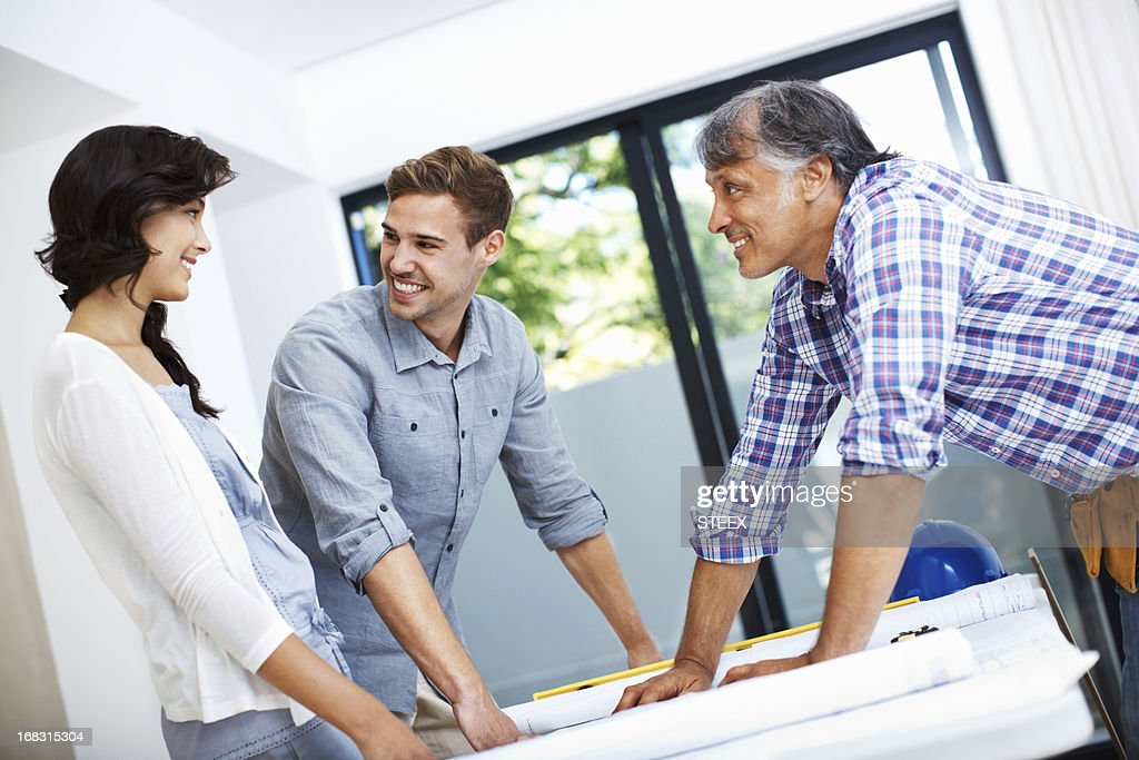 Attractive couple consulting architect : Stock Photo