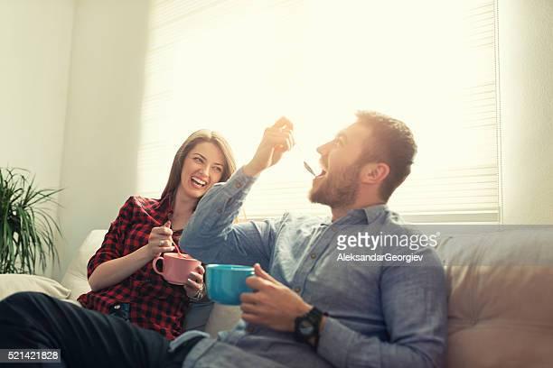 Attraktives Paar Essen Frühstück und Lachen am Morgen