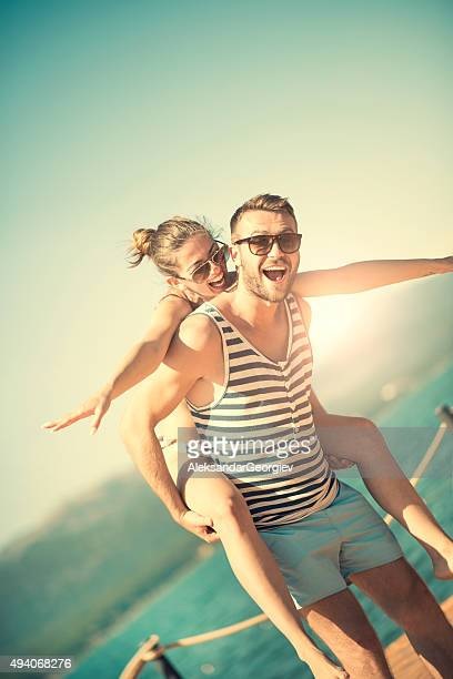 Joli Couple s'amuser avec tour d'enfants sur la plage