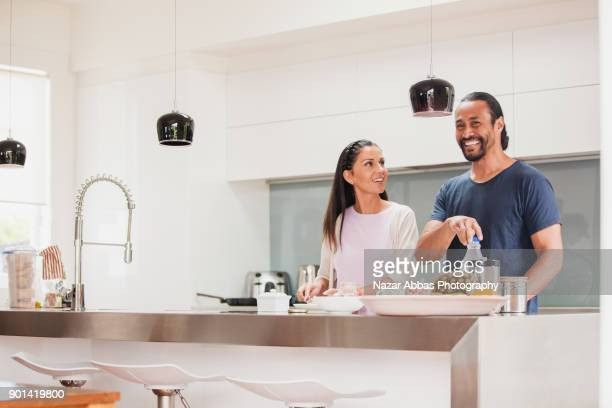 attractive couple having light moment in kitchen. - mid adult men stock pictures, royalty-free photos & images