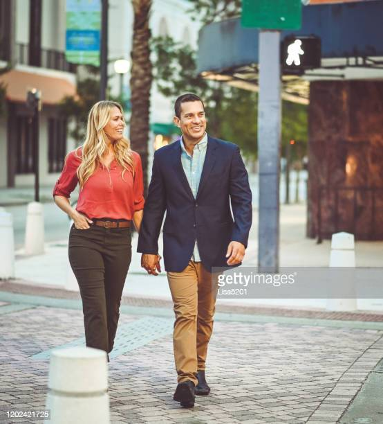 attractive couple holds hands while crossing street in a city - west palm beach stock pictures, royalty-free photos & images