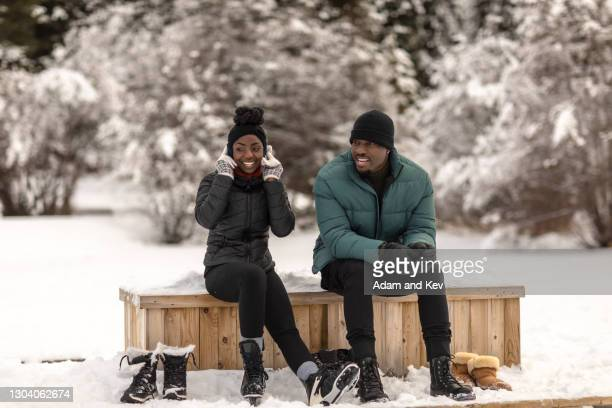 attractive couple sit at edge of frozen lake and contemplate ice-skating - holiday stock pictures, royalty-free photos & images