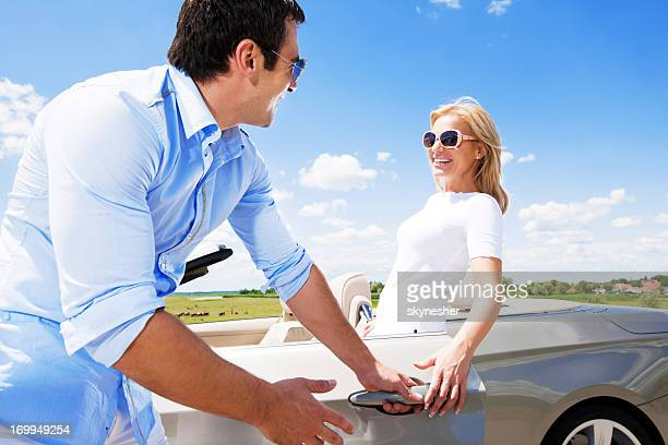 Attractive couple standing near Convertible car against the blue