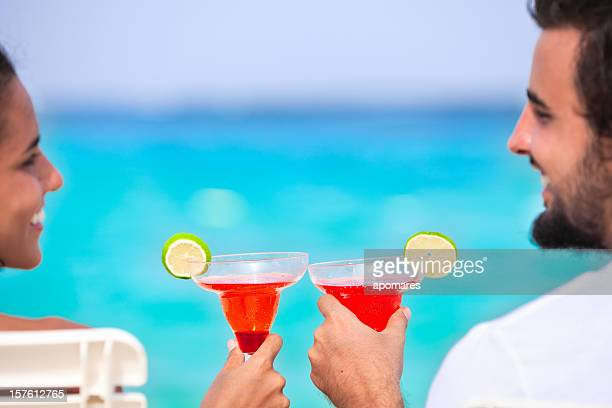 Attractive couple toasting on a Tropical turquoise beach