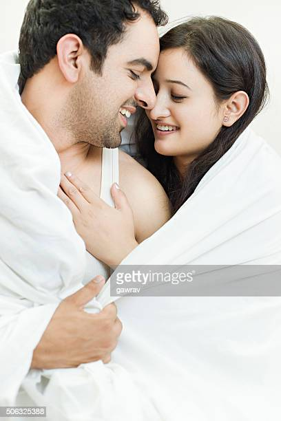 Attractive couple together on bed doing romance.