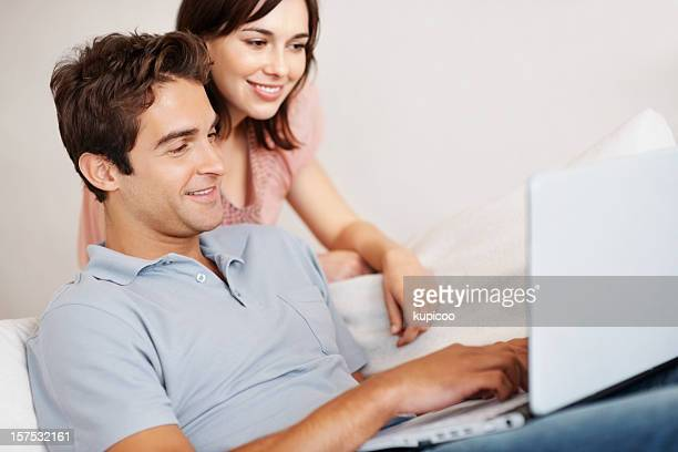 Attractive couple using a laptop at home